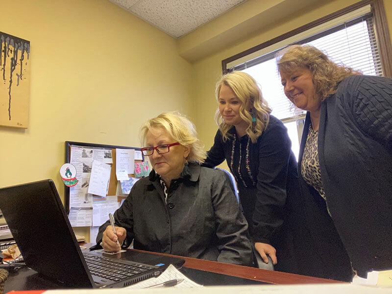 Staff members gathered around a laptop