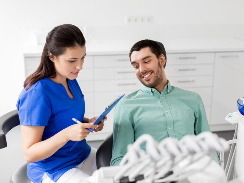 Smiling male patient sitting in a dental chair reviewing notes with a female dental assistant