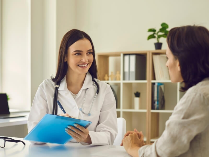 Smiling female doctor talking to a female patient in a private office