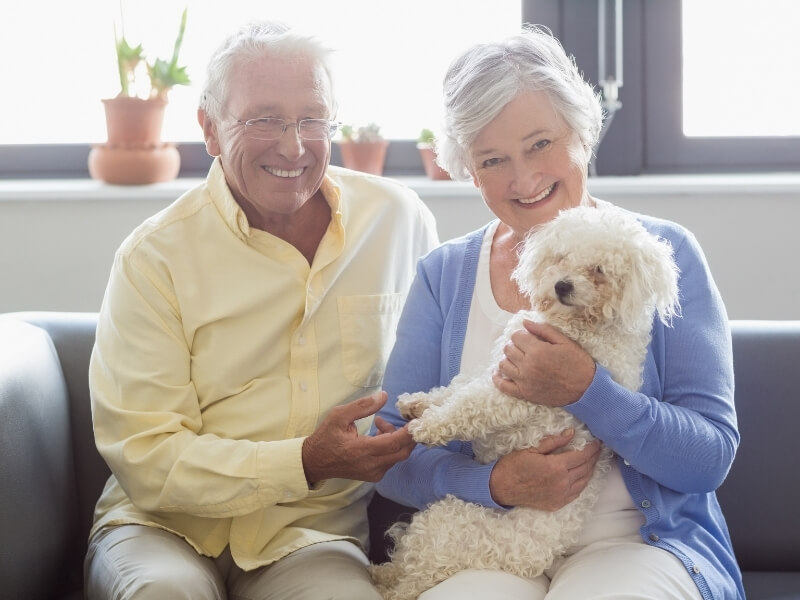 Smiling retired couple sitting on a couch while holding a lapdog