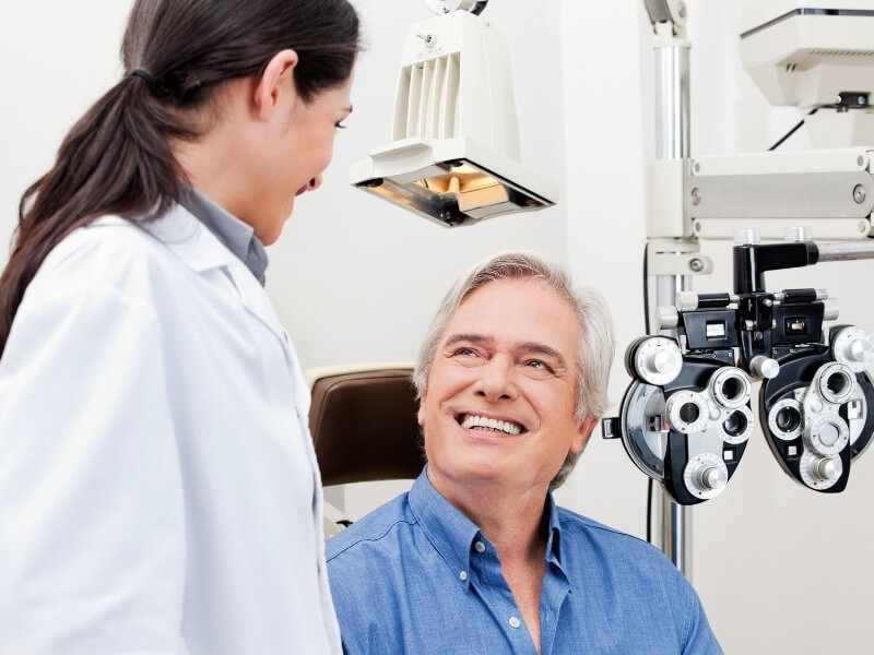 Older male patient smiling while looking up at his eye doctor